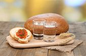 Composition with glasses of vodka  bread and red caviar on wooden table, on bright background
