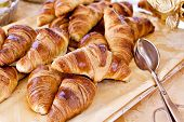 picture of tong  - Fresh homemade french croissants served for breakfast with pair of tongs - JPG