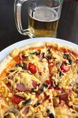 tasty pizza with glass of fresh beer