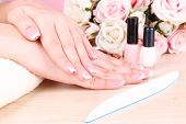 Beautiful woman hands with french manicure and flowers on wooden background