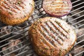stock photo of portobello mushroom  - Two portobello mushrooms marinated and grilling with purple onion - JPG