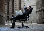Happy Business Man Sitting On Office Chair On Street With Computer