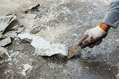 stock photo of scrape  - Close up worker hand scraping old paint on concrete floor - JPG