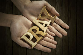 picture of pray  - Man holding pray word in palm with wooden background - JPG