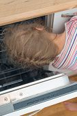 Little Girl Putting Head Into Dishwasher. Dangerous Situation At Home.