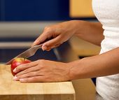 Female Hands Holding Cutting Apple In Kitchen