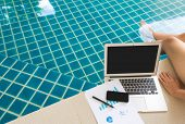 Woman working with laptop computer and financial documents sitting at swimming pool
