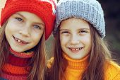 picture of 7-year-old  - Cute 7 years old girls wearing knitted winter sweaters walking outdoors in autumn - JPG