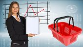 Businesswoman with shopping basket and graphs