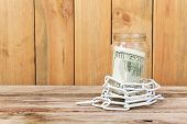 Money In A Glass Jar And Chain On A Wooden Table