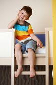 Happy little kid sitting on bunk bed, smiling.