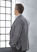 Caucasian businessman in suit looking at bright window, thinking, face not visible, hands in pocket.