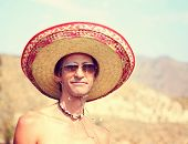 a man with a sombrero on his head at a local park on a hot summer day toned with a retro vintage ins