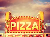 a pizza sign at the state fair on a hot sunny day right before dusk toned with a vintage retro insta