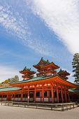 Green roof of Heian Jingu Shrine building under blue sky in Kyoto.