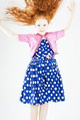 Happy Jumping Red-haired Caucasian Girl In Polka-dotted Dress Playing With Her Long Hair