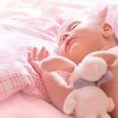 Newborn baby sleeps, relaxing in the bed, adorable healthy child dreaming, safe childhood concept