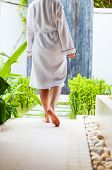 Close up of a woman wearing white robe walking at outdoor spa treatment room