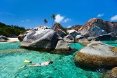 Young woman snorkeling in turquoise tropical water among huge granite boulders at The Baths beach ar
