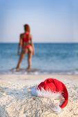 sexy woman in santa hat on sea beach