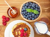 Pancakes with raspberry, blueberry, milk and honey syrup. On wooden table