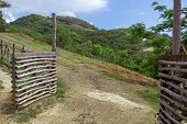 Open Gate And Road, Hill Landscape As Background