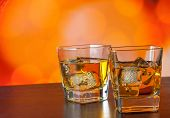 Whiskey Glass On Bar Table With Ice On Warm Atmosphere