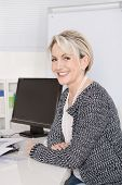 Happy Attractive Senior Female Manager In Portrait Sitting At Desk.