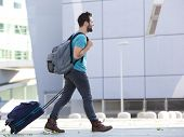 Young Man Walking Outdoors With Suitcase