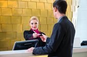 Man in Hotel check in at reception or front office being given key card