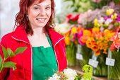 Female florist binding flower bouquet in shop