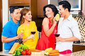 Asian friends cutting vegetables cooking together in domestic kitchen for dinner party, drinking win