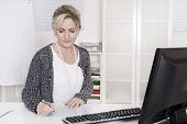 Senior Businesswoman Sitting At Desk Writing Something.