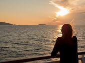 Girl looks at the sunset on the sea from the deck of a cruise boat. Corsica, mediterranean sea, Fran