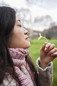 Side view of a young Asian woman smelling flower in park