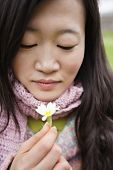 Close-up of a young Asian woman looking at flower