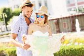 A picture of young couple of tourists standing with a map in the park