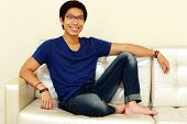 Happy asian man relaxing at home sitting on sofa