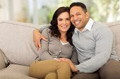 portrait of cute couple sitting on sofa at home
