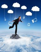 Businesswoman stepping and balancing against mountain peak through the clouds