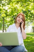 Pretty redhead using her laptop while phoning in the park on a sunny day