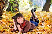 Happy cute woman outdoor portrait, lying in autumn park.