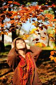Outdoor portrait of a pretty young brunette woman relaxing in autumn park.