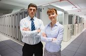 Confident data technicians looking at camera in large data center