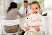 pretty little girl with teddy bear in pediatrician office