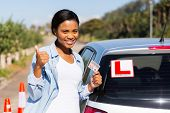 cheerful black woman showing a driving license she just got