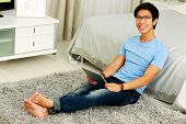 Cheerful asian man sitting on the carpet with tablet computer