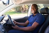 cheerful african man inside his new car