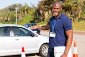cheerful young african driving instructor presenting a car