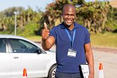 portrait of handsome african driving school instructor giving thumb up